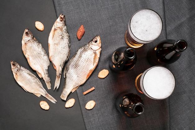 Płasko leżąca ryba z butelkami piwa i szklankami