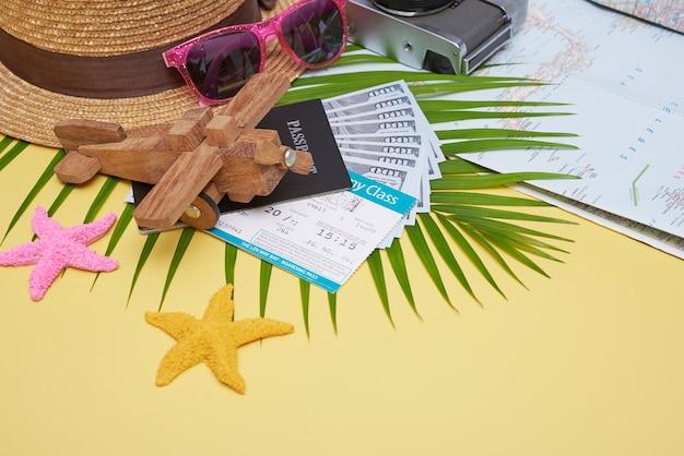 Płasko leżące akcesoria podróżne na żółtej powierzchni z liściem palmowym, aparatem, butem, czapką, paszportami, pieniędzmi, biletami lotniczymi, samolotami i okularami przeciwsłonecznymi. widok z góry, koncepcja podróży lub wakacji.