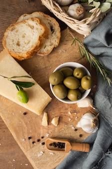 Płasko leżące oliwki parmezan i czosnek na desce do krojenia