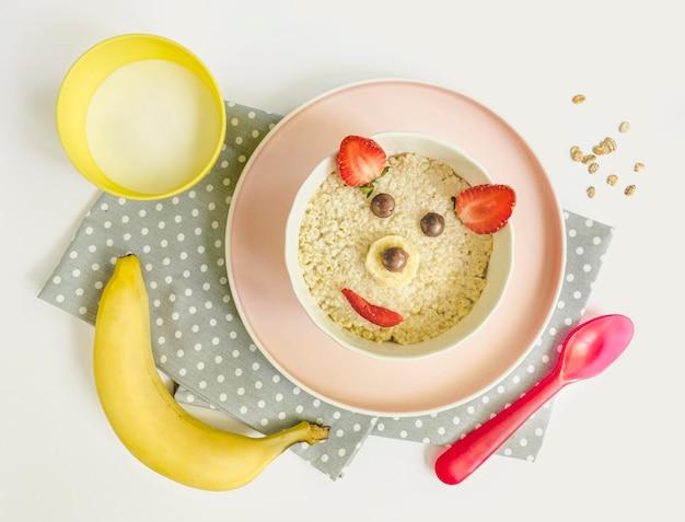 Płasko leżące płatki zbożowe w kształcie niedźwiedzia i szklanka mleka