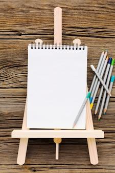 Płasko leżał pusty biały notatnik i ołówki