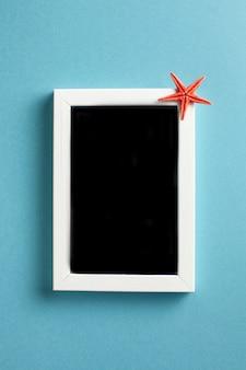 Płasko leżała czerwona rozgwiazda na pustej ramce na niebiesko photo