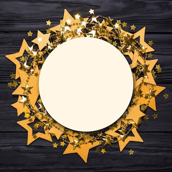 Płasko leżała pusta okrągła ramka z dużymi i małymi gwiazdkami konfetti. złote koraliki w postaci gwiazdek.