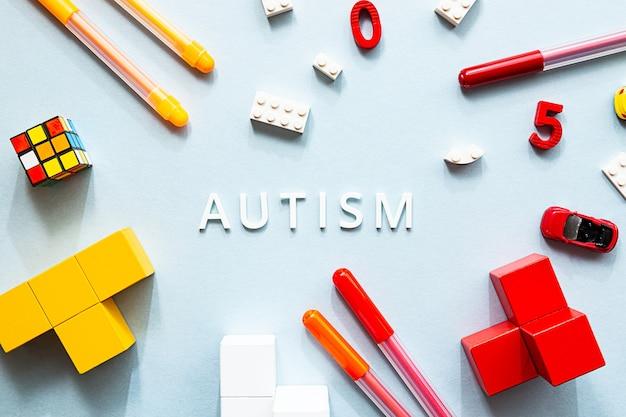 Płasko leżało białe słowo autyzm z kostkami, puzzlami, kolorowymi markerami i zabawkami