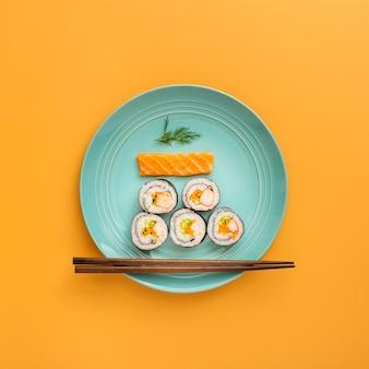 Płasko leżało nigiri i maki sushi z pałeczkami