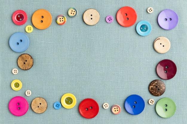 Płasko leżały kolorowe guziki na tkaninie