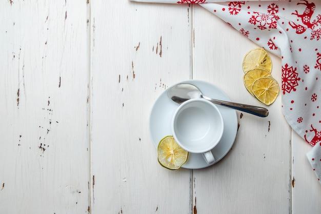 Płasko położona biała pusta ceramiczna filiżanka na spodku i łyżeczka suszonych plasterków limonki