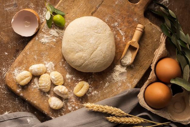 Płasko układane ciasto i gnocchi ziemniaczane na desce do krojenia