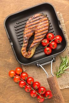 Płasko ułożona ryba z grilla z pomidorami