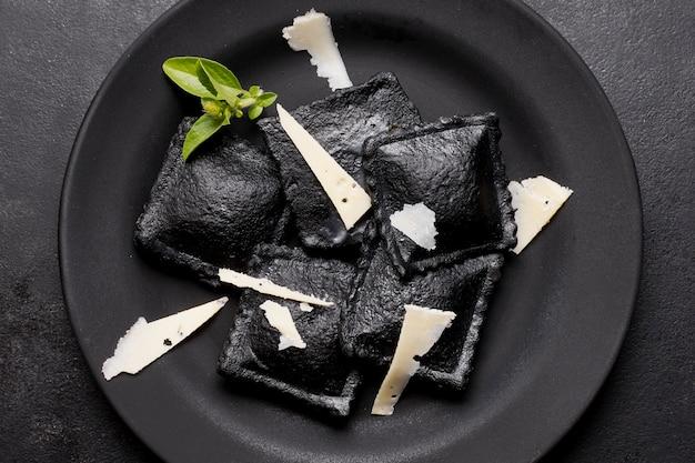 Płasko ułożone czarne ravioli na ciemnym talerzu z plasterkami sera