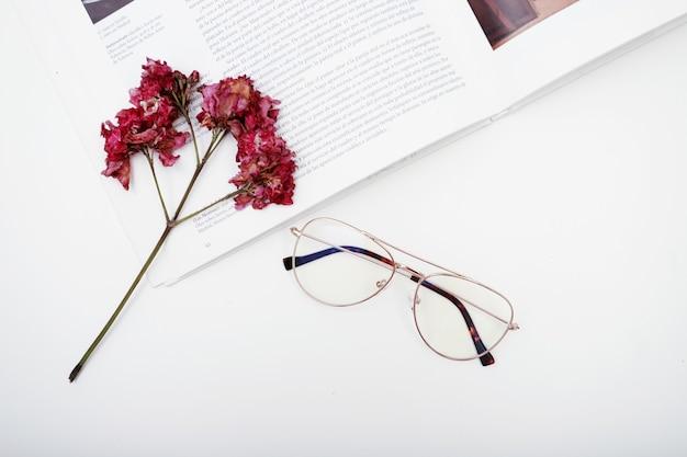 Płasko ułożone okulary, aby zobaczyć książkę i zwiędłe kwiaty z białą przestrzenią