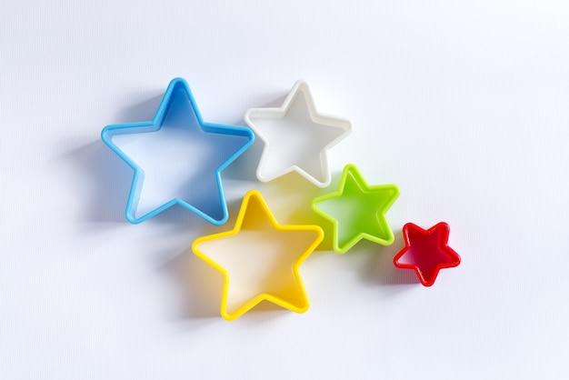 Płasko ułożone ozdobne kolorowe plastikowe foremki w kształcie gwiazdek do gotowania domowego ciasta bożonarodzeniowego na białym tle