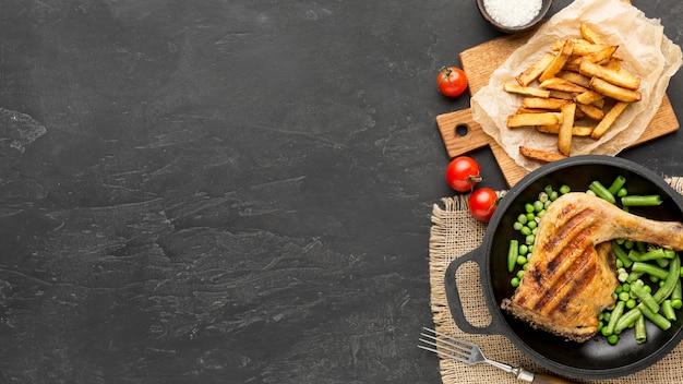 Płasko ułożone pieczone strąki kurczaka i grochu na patelni z ziemniakami i miejscem do kopiowania