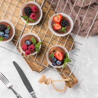 Płasko ułożone smaczne muffinki z owocami leśnymi i sztućcami