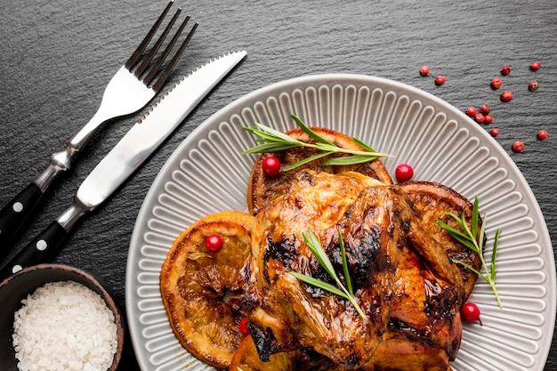 Płasko ułożony pieczony kurczak i plastry pomarańczy na talerzu ze sztućcami