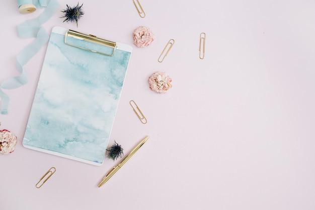 Płasko ułożony schowek, pąki róż, niebieska wstążka, złoty długopis i spinacze w kolorze jasnoróżowym