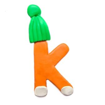 Plastelina pomarańczowa litera k alfabetu w zimowej zielonej czapce na białym tle