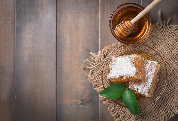 Plaster miodu na naczyniu z czerpakiem liści i miodu na tle drewna i przestrzeni kopii, produkty pszczele według koncepcji ekologicznych naturalnych składników