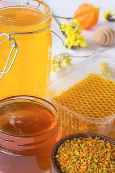 Plaster miodu, pyłek kwiatowy i słoiki z miodem. miód i kwiaty