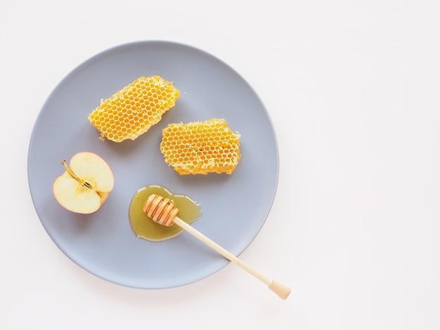 Plaster miodu z łyżką i plasterkiem jabłka na talerzu produkty naturalne