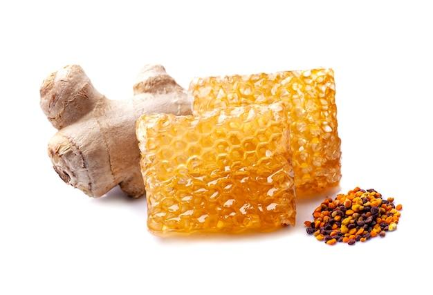Plaster miodu z pyłkiem i korzeniem imbiru na białym tle. zdrowy składnik żywności.