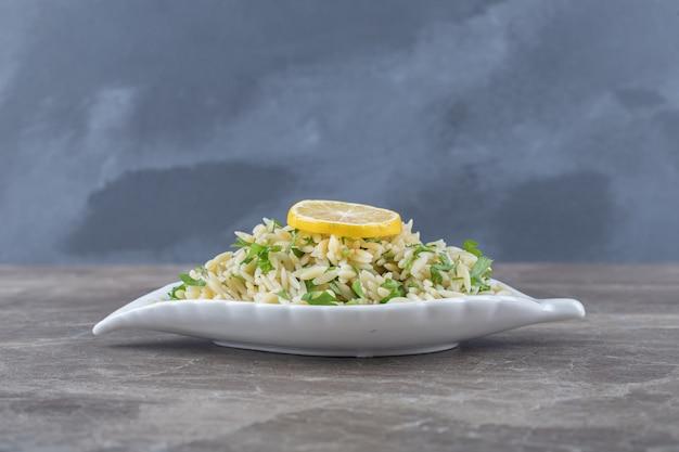 Plasterek cytryny na makaronie z zielonymi warzywami, na marmurowej powierzchni.