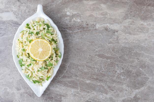 Plasterek cytryny na makaronie z zielonymi warzywami, na marmurowym tle.