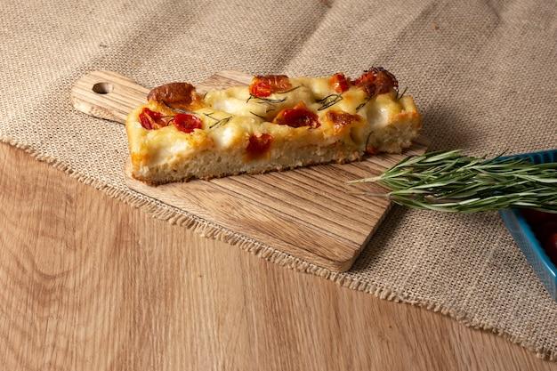 Plasterek focaccii z rozmarynem, oliwą z oliwek i pomidorami na drewnianym stole
