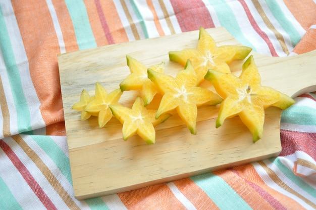 Plasterek gwiezdnych owoców na drewnianej desce do krojenia