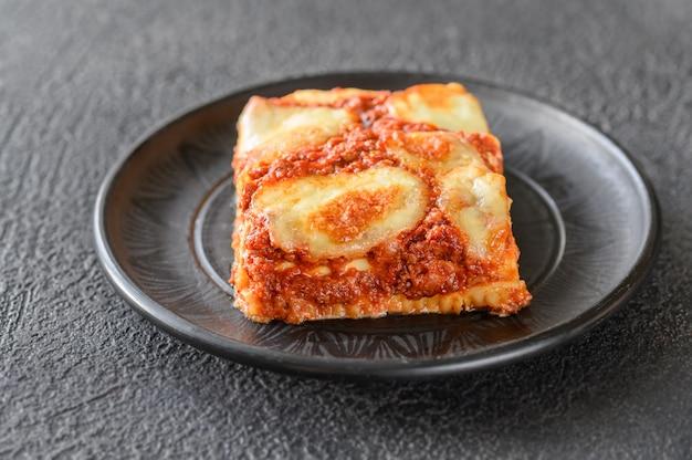 Plasterek lasagne na czarnym talerzu