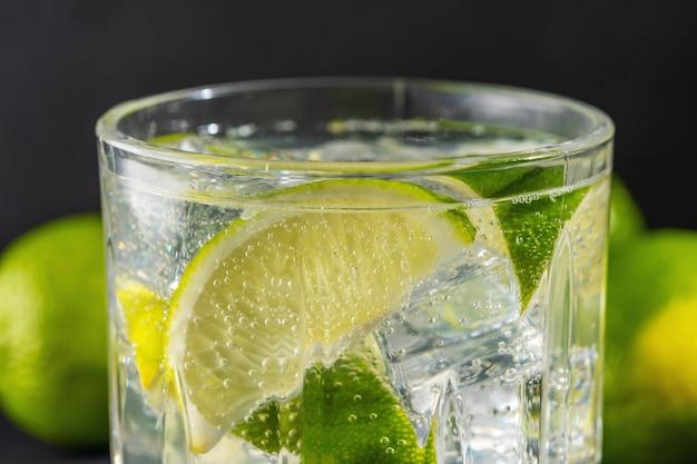 Plasterek limonki z gazowaną wodą w szklance.