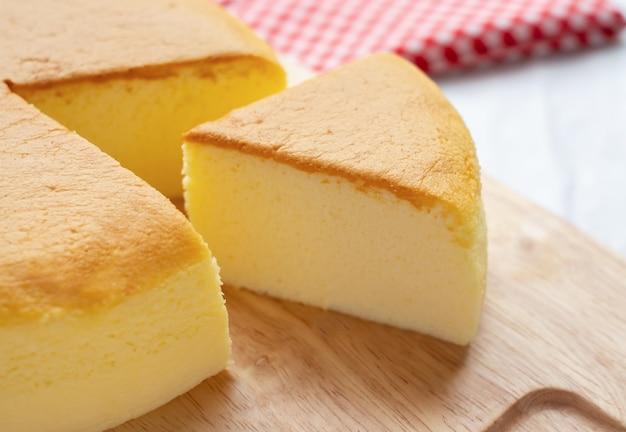 Plasterek masła tort na drewnianym tle
