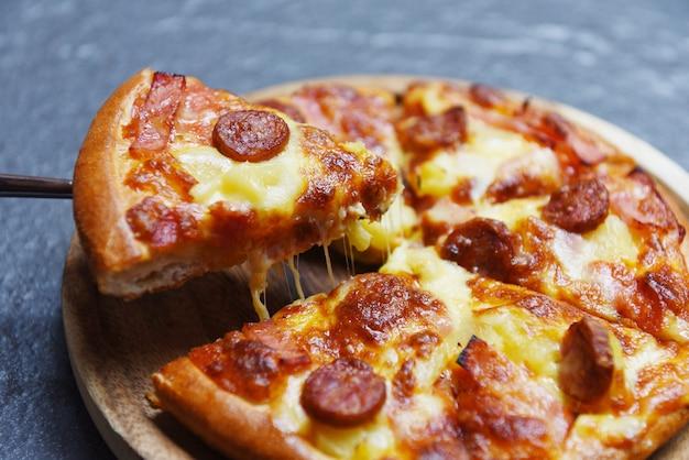 Plasterek pizzy na ciemnym tle