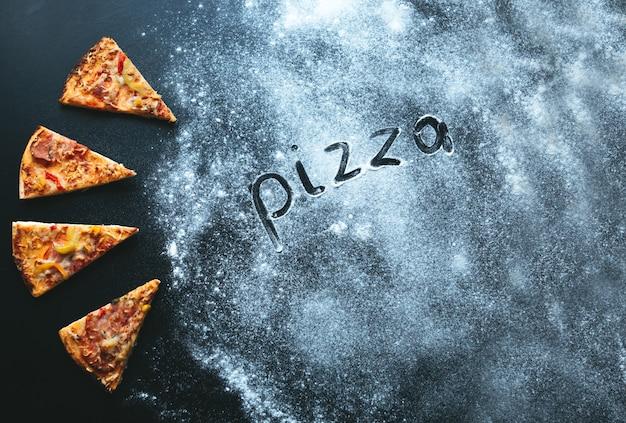 Plasterek pizzy na czarnym tle, z miejscem na tekst i mąkę. pizza tekstowa włochy