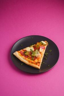 Plasterek pizzy z pepperoni, salami, roztopionym serem mozzarella, marynatami i koperkiem w czarnej płycie na różowym fioletowym tle, kąt widzenia