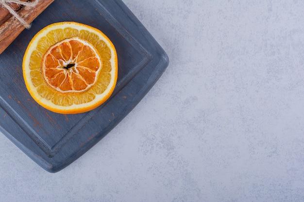 Plasterek pomarańczy na ciemnej desce z aromatycznymi laskami cynamonu.