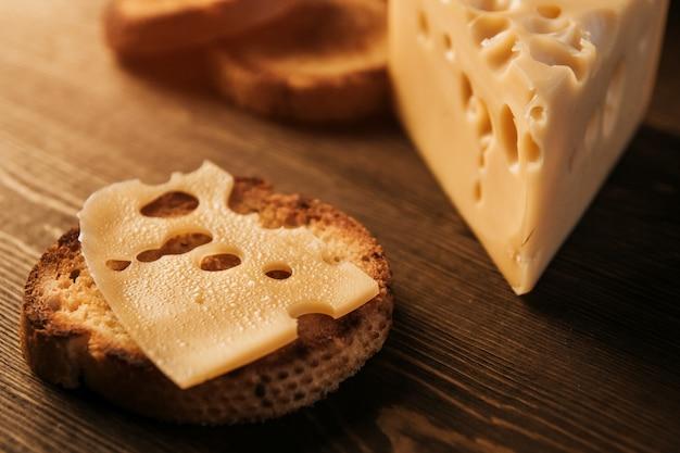 Plasterek przepoconego sera i smażonego chleba na drewnianym stole. ser z dużymi dziurami. kanapka z serem.