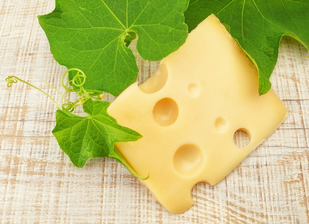 Plasterek pysznego holenderskiego sera na tle liści winogron.