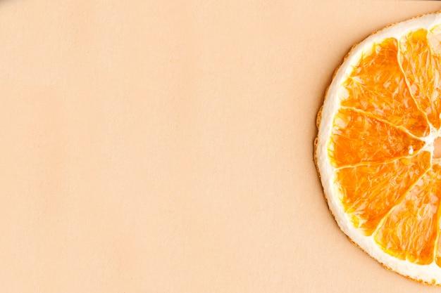 Plasterek suszonej pomarańczy na jasnobrązowym tle z miejscem na tekst. minimalizm, koncepcja żywności.