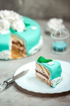 Plasterek turkusowego ciasta ozdobiony białymi różami i zielonymi liśćmi