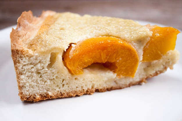 Plasterka brzoskwiniowego ciasta morelowego na białym talerzu
