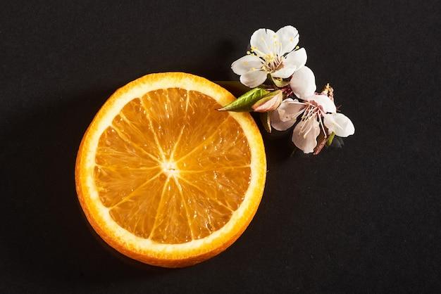 Plasterka dojrzałych pomarańczowych owoców cytrusowych samodzielnie na czarno.