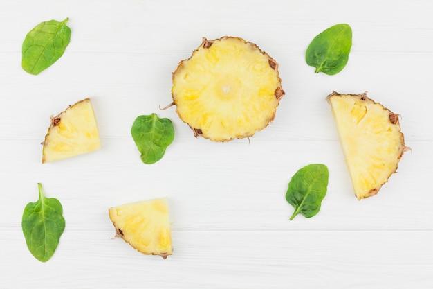Plasterki ananasa wśród zielonych liści roślin