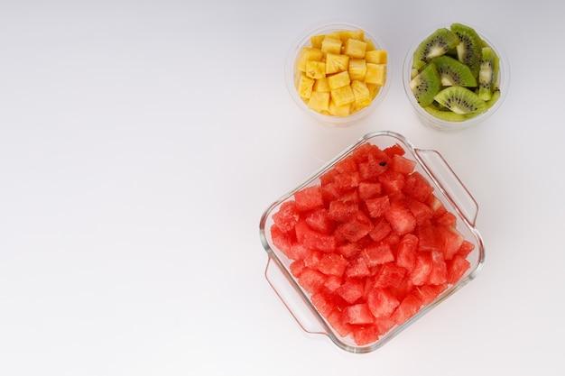 Plasterki arbuza, ananasa i kiwi ułożone w dwóch przezroczystych szklankach z białym tłem, na białym tle