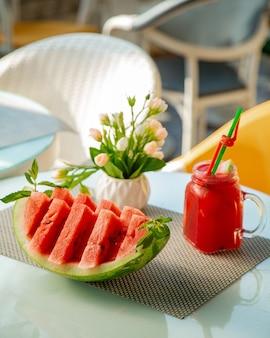 Plasterki arbuza i szklanka z sokami arbuzowymi