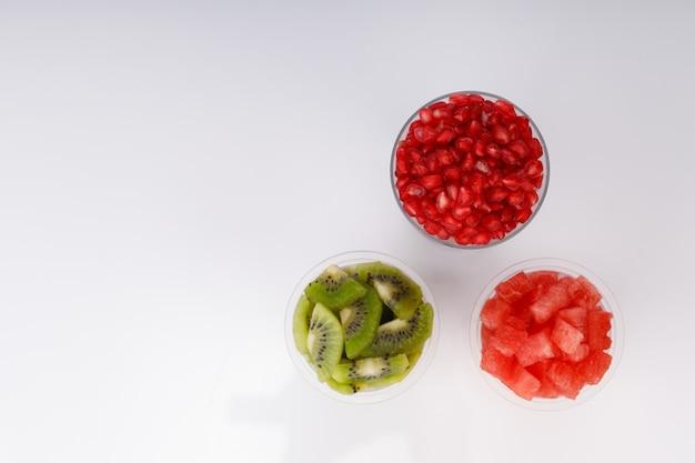 Plasterki arbuza, pomogrenatu i kiwi ułożone w dwóch przezroczystych szklankach z białym tłem, na białym tle