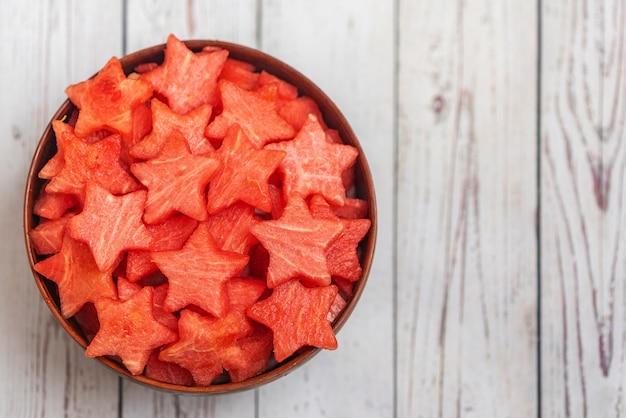 Plasterki arbuza w kształcie gwiazdy w misce na jasnym drewnie. widok z góry,