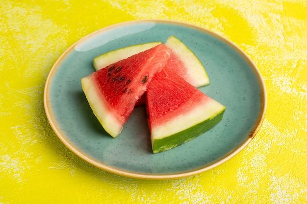 Plasterki arbuza wewnątrz zielonego talerza na żółto