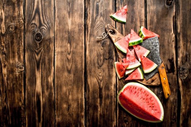 Plasterki arbuza z siekierą. na drewnianym tle.