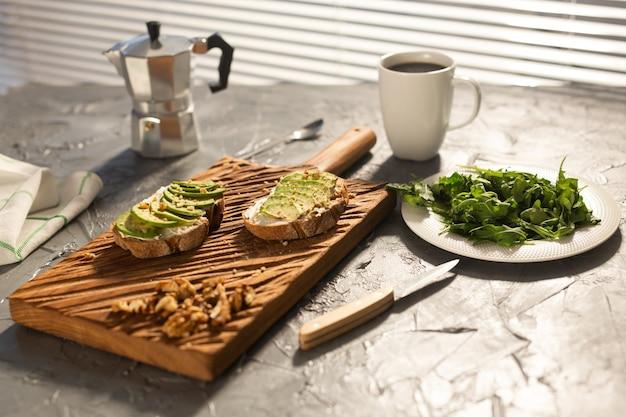 Plasterki awokado na chleb tostowy z orzechami i kawą śniadanie i pojęcie zdrowej żywności